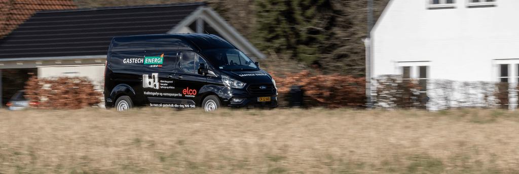 sort gastech service varebil køre på landevej bag mark og foran huse